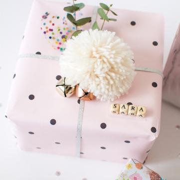 boite-cadeau-carton-avec-emballage-de-papier-rose-à-pois-noirs-pompon-blanc-ficelle-grise-clochettes-et-branches-vertes-e1511450373672