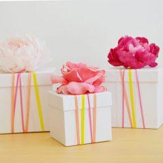 boite-cadeau-carton-blanche-avec-decoration-de-bandes-colorées-et-une-fleur-fraiiches-sur-le-couvercle