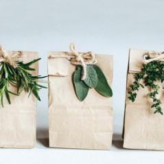 cadeau-dans-un-sachet-kraft-avec-ficelle-pour-fermeture-et-brins-de-plantes-vertes-pour-décoration-naturelle