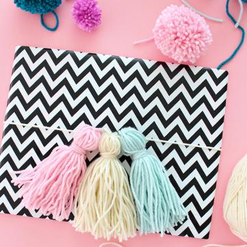 emballer-cadeau-idée-de-décoration-paquet-de-cadeau-papier-motis-chevron-noir-et-blanc-et-decoration-de-pompon-à-franges-jaune-rose-et-bleu-e1511424656965