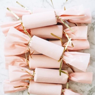 papier-cadeau-noel-rose-et-emballage-en-forme-de-bonbon-avec-des-bouts-entortillés-et-serrés-avec-un-ruban-doré-idée-originale-cadeau-femme-simple-e1511447220273